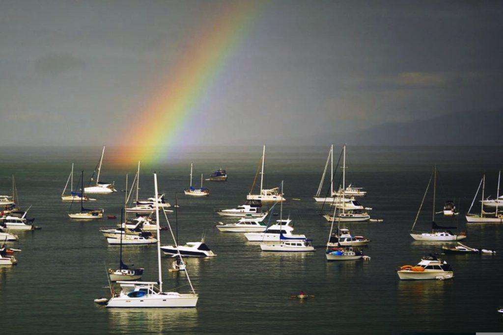 Rainbow over yachts moored in an ocean bay.